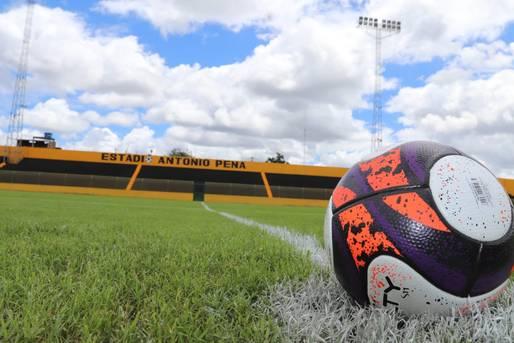 Gramado do Estádio de Catu, com uma bola em primeiro plano e prédio amarelo ao fundo